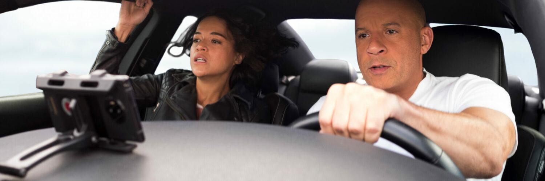 Letty und Dom im Innenraum eines Autos. Dom lenkt während Letty erschrocken aussieht.