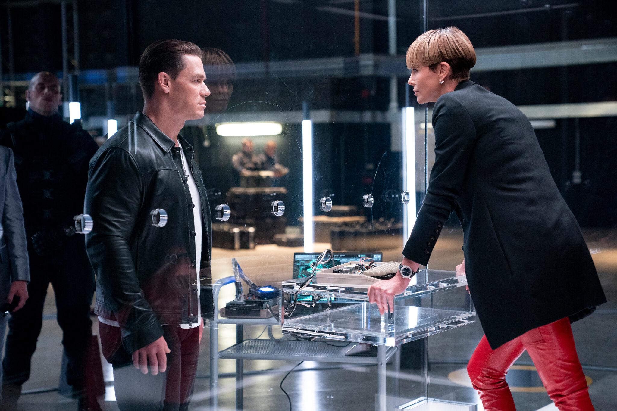 Jakob (John Cena) steht vor Cipher (Charlize Theron) und wird von einer Glasscheibe von ihr getrennt. Dazwischen sieht man einige alte Computerteile auf einem Glastisch. Fast & Furious 9