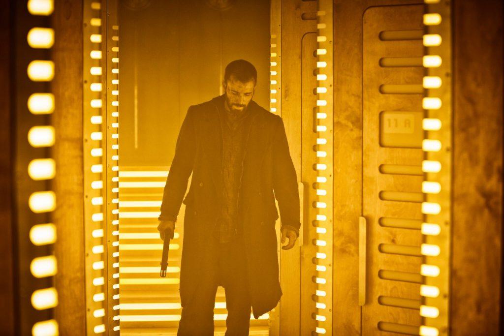 Chris Evans steht in Snowpiercer mitgenommen in einer Tür zwischen zwei Gängen.