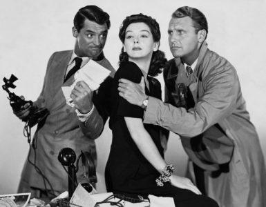 Cary Grant mit zwei Schauspielkollegen hält ein Telefon fest