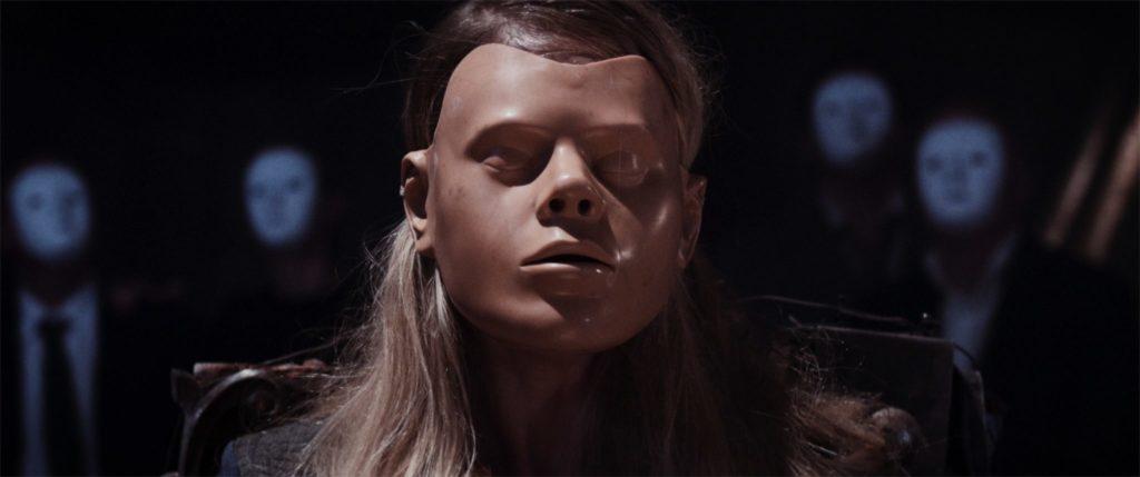 Agnes hat eine ausdruckslose Maske auf und im Hintergrund sind weitere Menschen mit Masken zu sehen