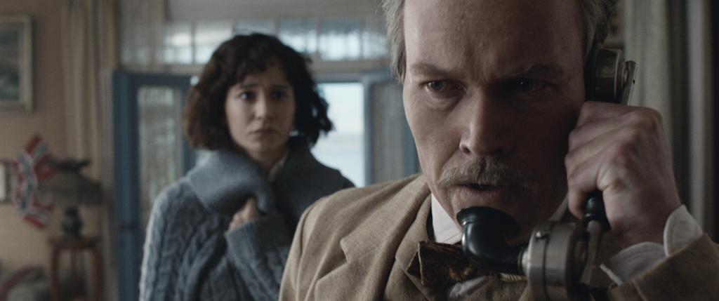 Leon und Bess in Roald Amundsens Haus, Leon telefoniert, Bess im Hintergrund | Amundsen - Wettlauf zum Südpol