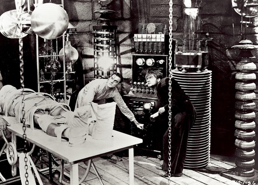 Dr. Frankenstein und sein Gehilfe Fritz starren gebannt auf die Appatur zur Übertragung des Blitzes auf den noch toten Körper, der von einer Plane verhüllt darunter auf der Bahre liegt - Univeral Horror Filme
