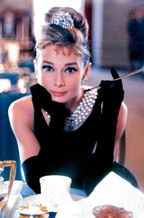 Audrey Hepburn am Tisch sitzend mit Perlenkette und Zigarette in der Hand