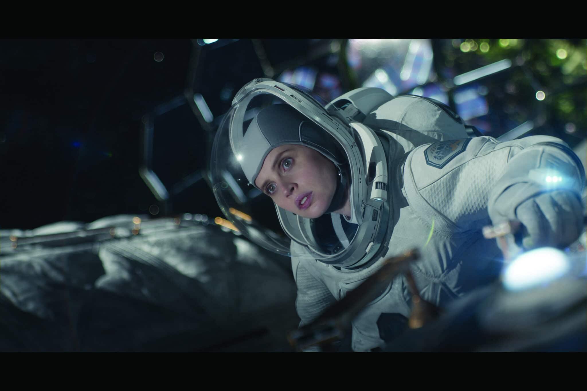 Sully (Felicity Jones) in einem weißen Raumanzug mit Glashelm.