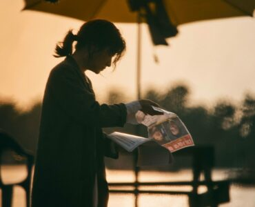 Jung-Yeon (Lee Young-ae) steht unter einem Sonnenschirm im Schatten und blättert in einem Dokument mit einem Fandungsbild auf der Titelseite.