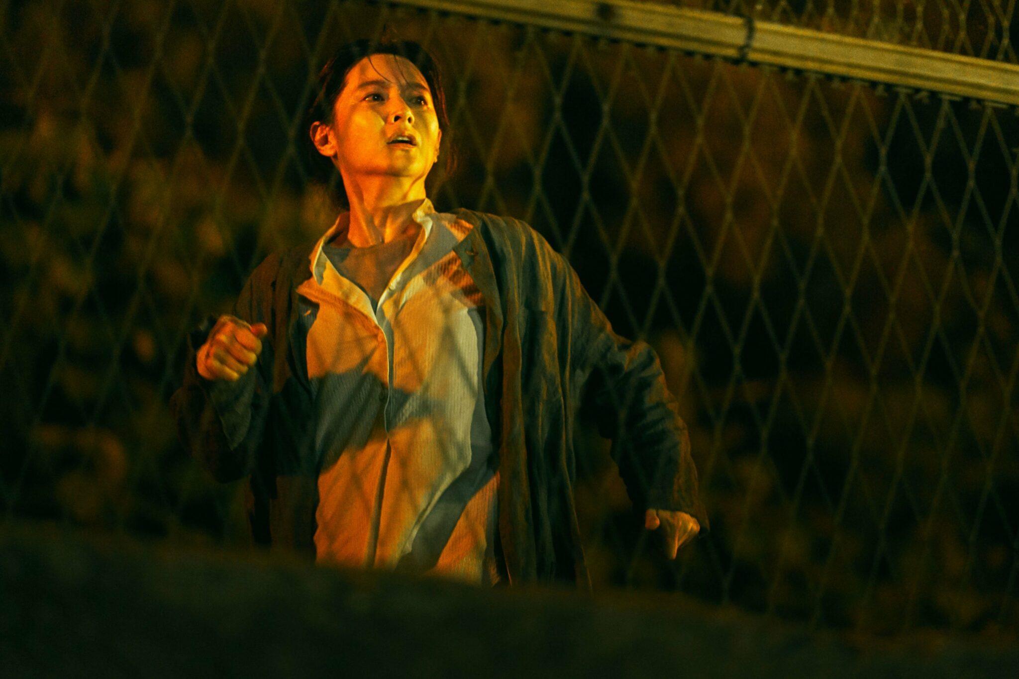 Jung-Yeon (Lee Young-ae) steht mit erschrockenem Gesichtsausdruck nachts hinter einem Drahtzaun.