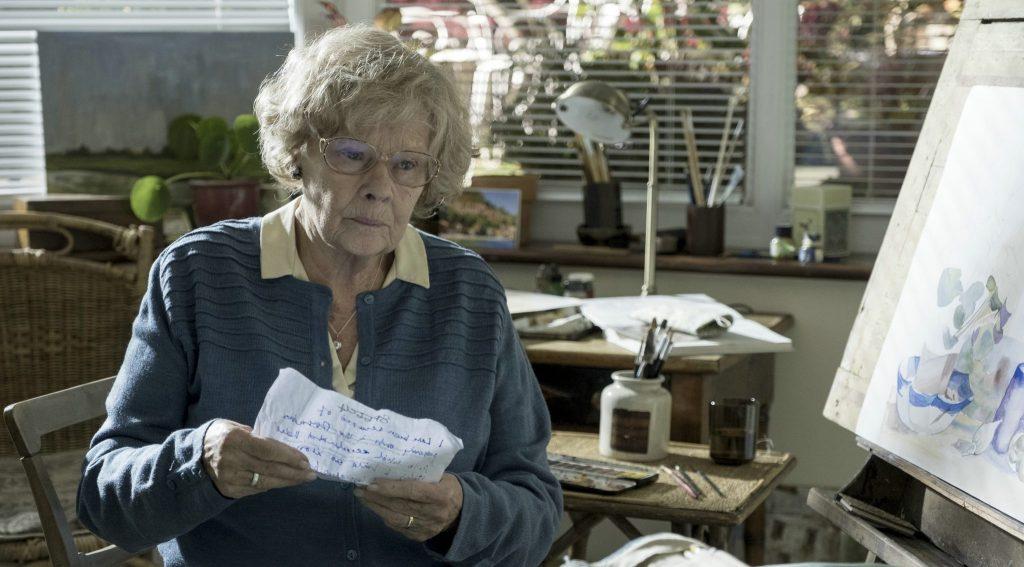 Joan beginnt sich beim Lesen eines alten Briefes zu erinnern. Sie sitzt vor einer Staffelei, an der sie an einem Aquarell gearbeitet hat. Sie hält den handgeschrieben Brief in beiden Händen.