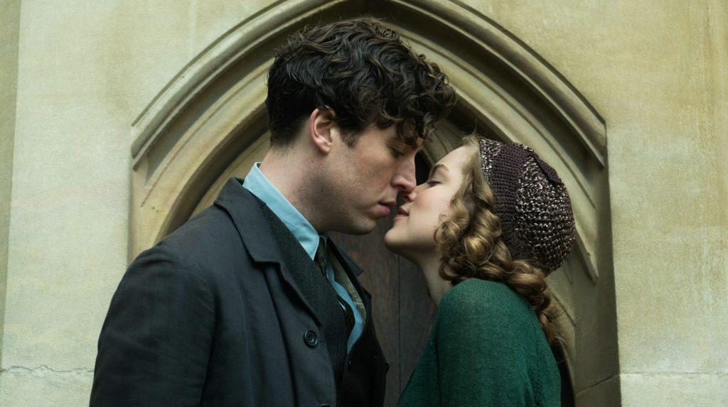 Die junge Joan (Sophie Cookson) verfällt dem attraktiven Leon (Tom Hughes) und küsst ihn. vor einem Portal der Universität Cambridge. Sie steht rechts im Bild und blickt zu ihm auf. | Geheimnis eines Lebens