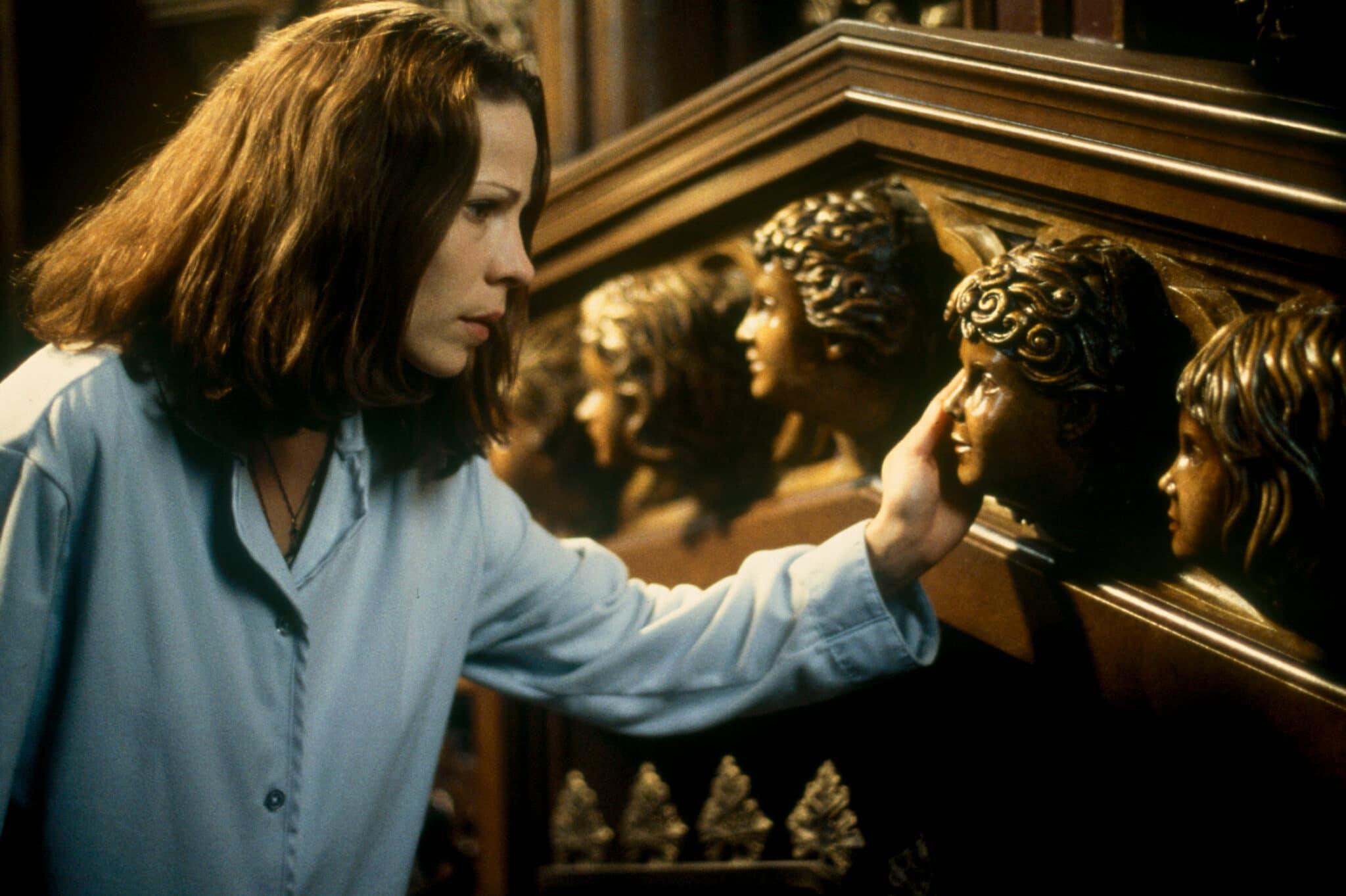 Lili Taylor spielt Eleanor Vance in das Geisterschloss. Sie steht im Nachthemd vor einem Kamin mit glänzenden Holzvertäfelung, aus der mehrere Kinderköpfe zur Dekoration herausgearbeitet sind. Sie berührt eines der Gesichter mit der linken Hand und zeigt dabei einen nachdenklichen Gesichtsausdruck.