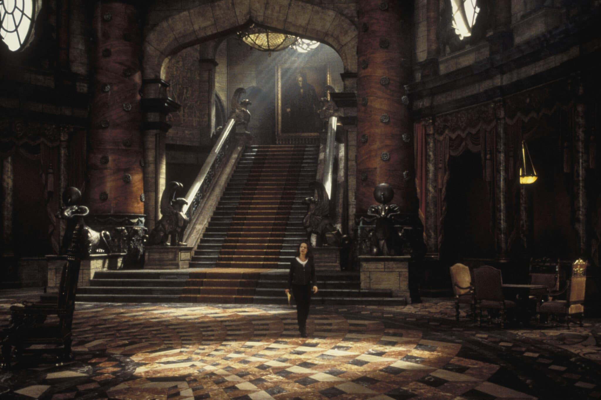 In Das Geisterschloss läuft Lili Taylor durch die riesige Eingangshalle. Überall sind schwere Teppiche, Holzornamente und Figuren zu sehen, die dem ganzen Saal ein edles Erscheinungsbild verleihen.