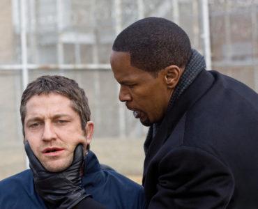 In Gesetz der Rache packt Jamie Foxx den knienden Gerard Butler am Hals