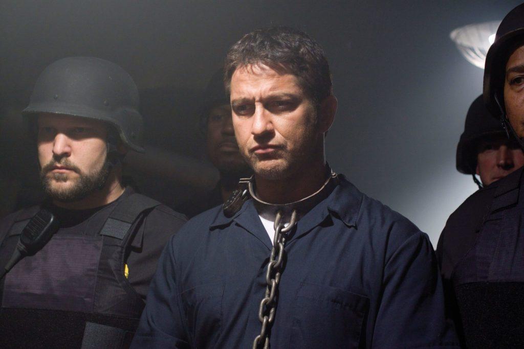 Gerard Butler steht in Häftlingskleidung zwischen zwei schwer bewaffneten Einsatzleuten der Polizei