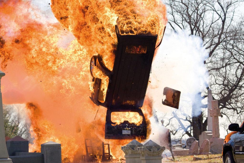 Ein explodierendes Auto fliegt auf einem Friedhof durch die Luft in Gesetz der Rache