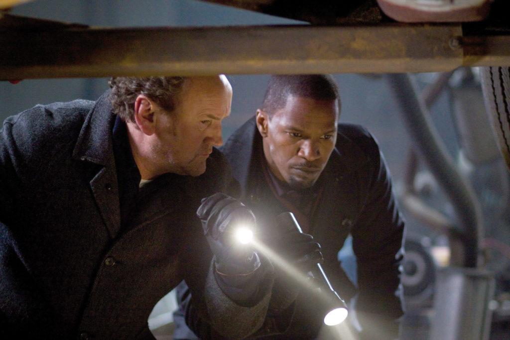 Jamie Foxx als Nick Rice und Colm Meaney als Dunnigan stehen mit erhobener Taschenlampe in einer Werkstatt