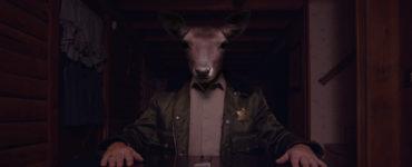 """Ein Polizist mit dem Kopf eines Rehs sitzt an einem Tisch, auf dem ein Messer liegt, in """"Ghost Cabin""""."""