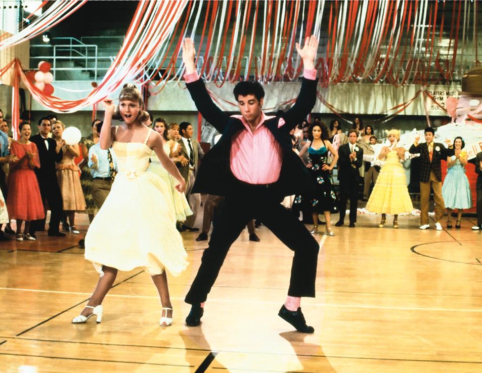Travolta mit nach oben gestreckten Armen auf der Tanzfläche in Grease