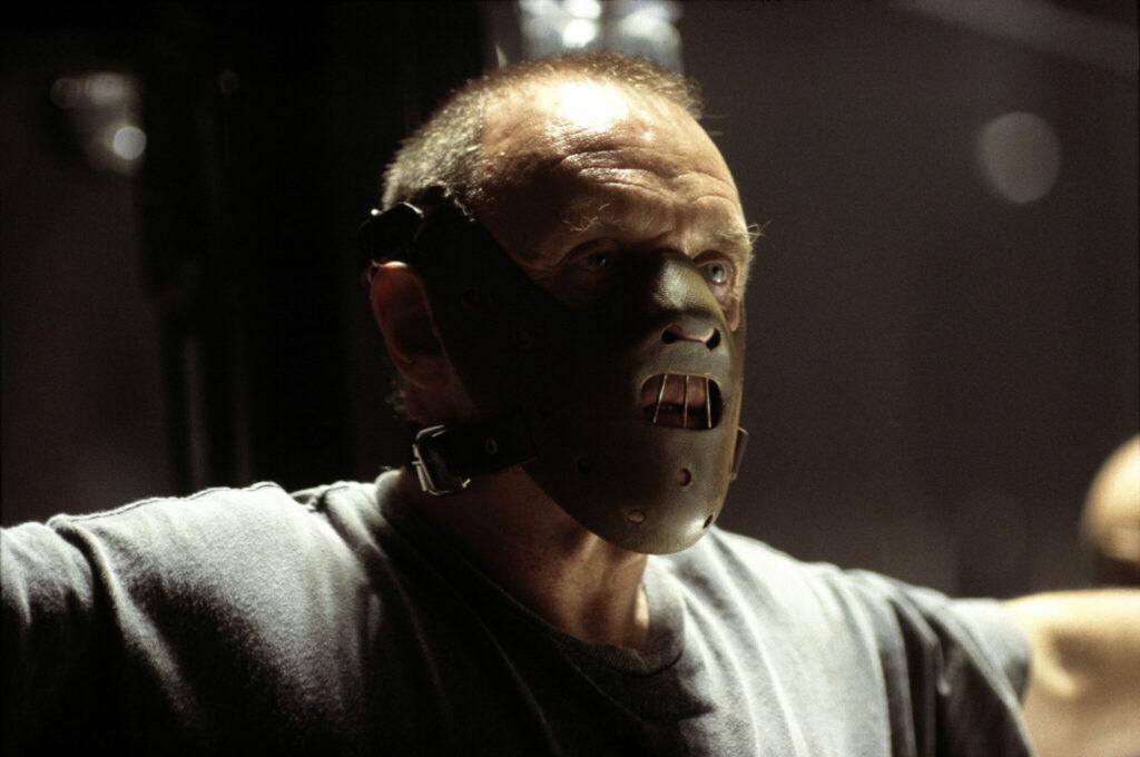 Eine Großaufnahme von Anthony Hopkins als Hannibal Lecter, der gefesselt ist und einen Maulkorb trägt - Die 10 besten Kannibalenfilme