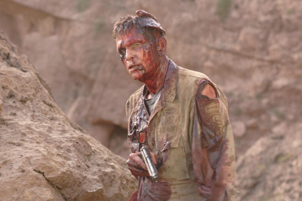 Ein Soldat steht blutüberströmt und mit klaffender Kopfwunde in der Wüste und trägt eine Pistole in The Hills Have Eyes 2
