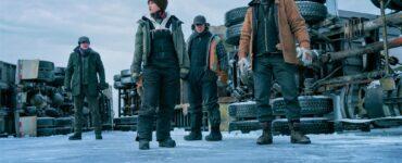 Die Crew steht vor den umgekippten Trucks und blickt auf das dünne Eis in The Ice Road