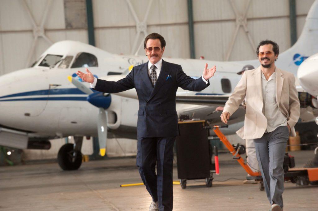 Bryan Cranston und John Leguizamo laufen in einem Flugzeughangar auf die Kamera zu, sie sehen beide freundlich aus