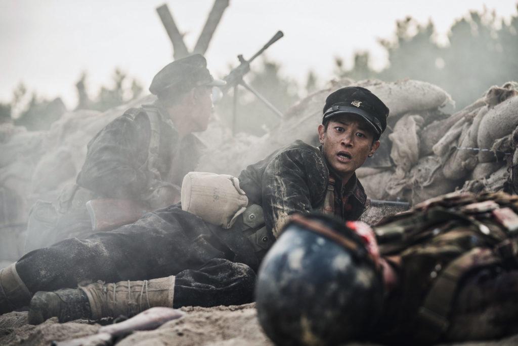 Am Ufer von Jangsari liegen zwei südkoreanische Soldaten in Deckung, während sie beschossen werden. Einer Schaut schockiert zu seinem toten Kameraden.