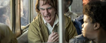 Joaquin Phoenix als Arthur Fleck sitzt lachend im Bus