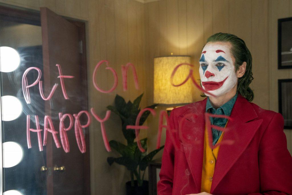 Arthur Fleck als Joker vor dem Spiegel auf dem geschrieben Steht: Put on a happy face