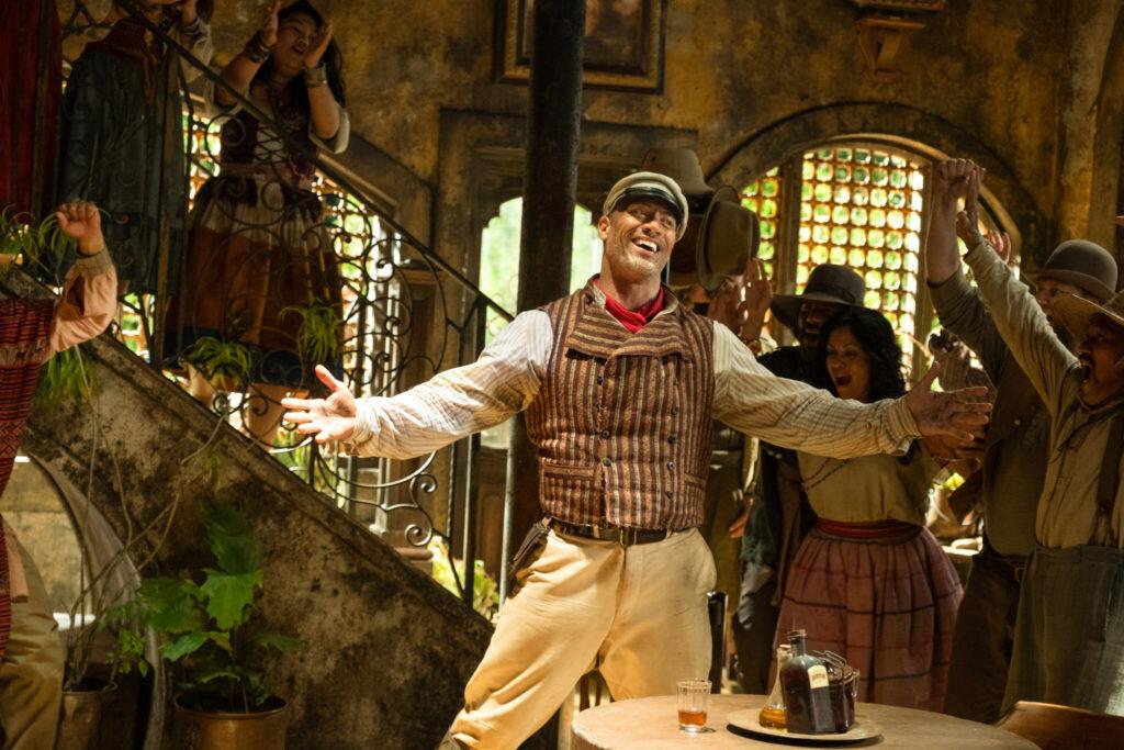 Dwayne Johnson als charismatischer Skipper Frank. Er steht inmitten eines gut besuchten Lokals. Alles ist im typisch, nostalgischen Look. Er trägt eine Pumphose mit brauner Weste und hält die Arme eröffnend und mit einem Lächeln von sich - in Jungle Cruise.