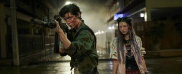 Zwei Darstellerinnen, eine mit Waffe, schauen an der Kamera vorbei in Kate