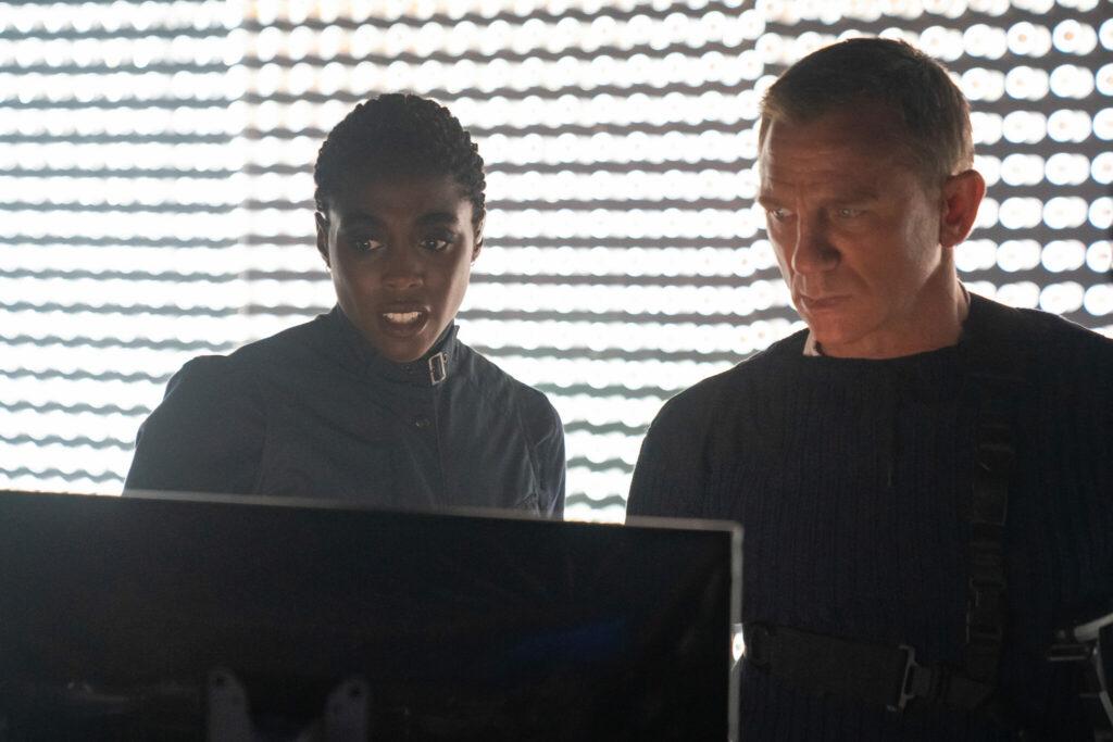 Lashana Lynch als Nomi und Daniel Craig als James Bond starren auf einen Bildschirm in Keine Zeit zu sterben