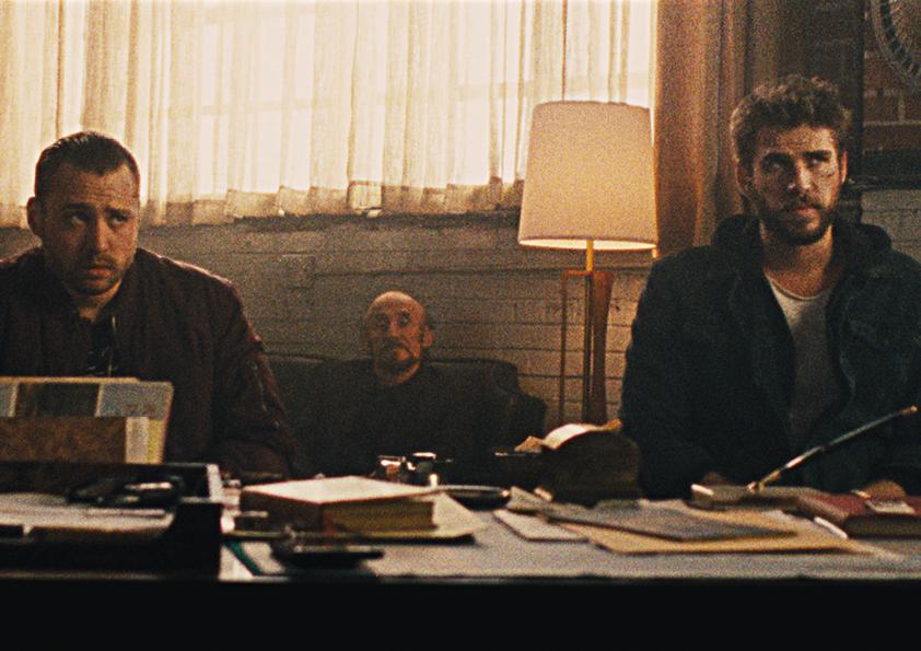 Emory Cohen und Hemsworth sitzen vor einem Schreibtisch in Killerman