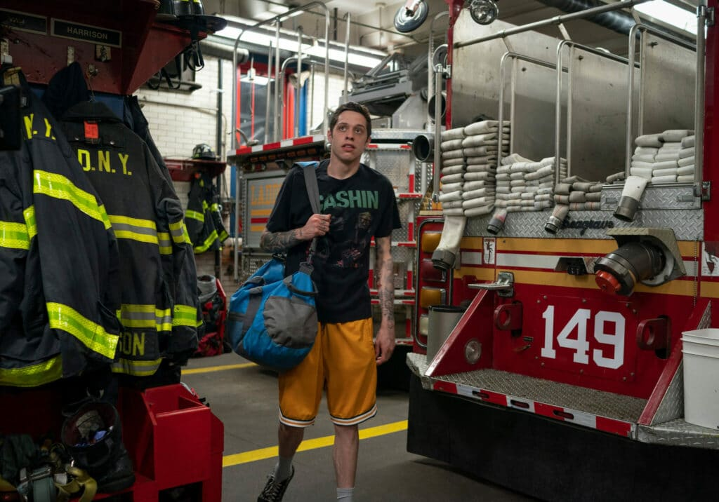 Scott Carlin mit geschulterter Reisetasche in der Garage der Feuerwache in The King of Staten Island.