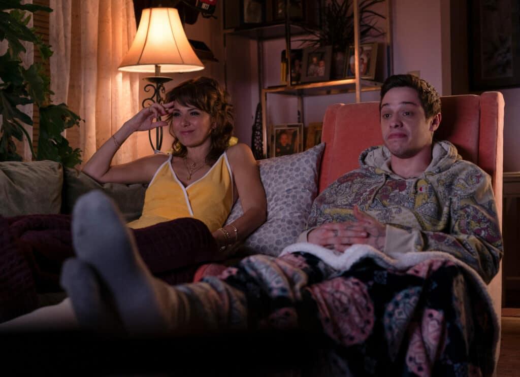 Pete Davidson als Scott Carlin und Marisa Tomei als Margie Carlin sitzen gemeinsam in Sesseln vor dem Fernseher.