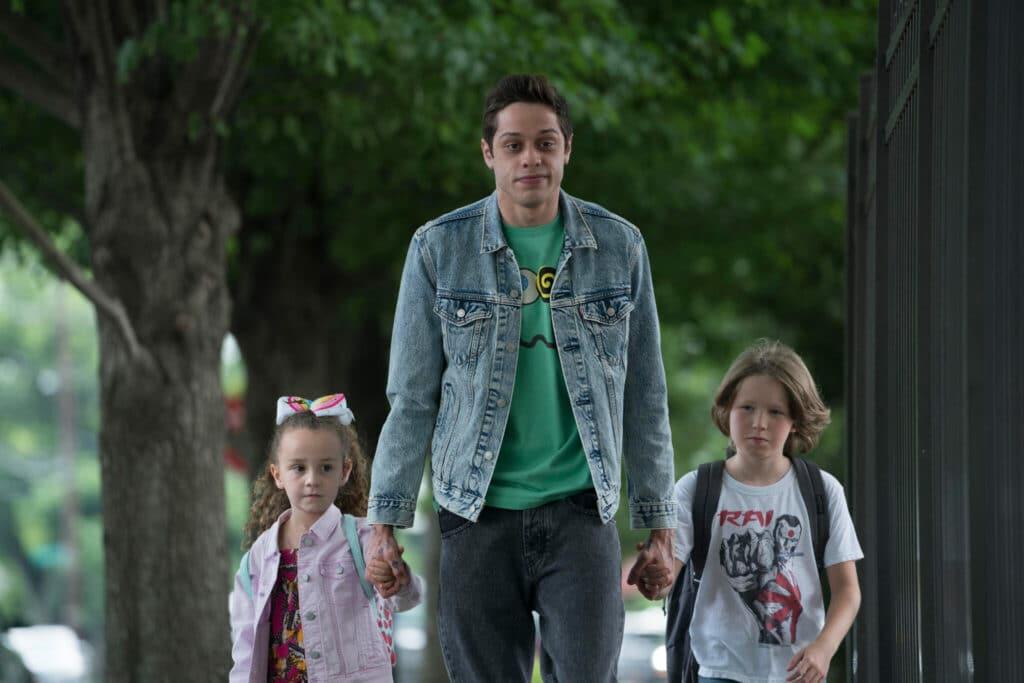 Pete Davidson als Scott Carlin hält zwei Kinder an der Hand auf einem Gehweg in The King of Staten Island.
