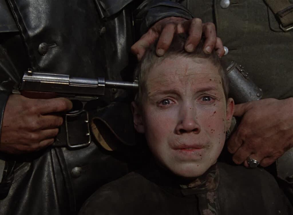 Fljoras schaut verstört und verängstigt, während ihm seitlich eine Pistole an die Schläfe gehalten wird.