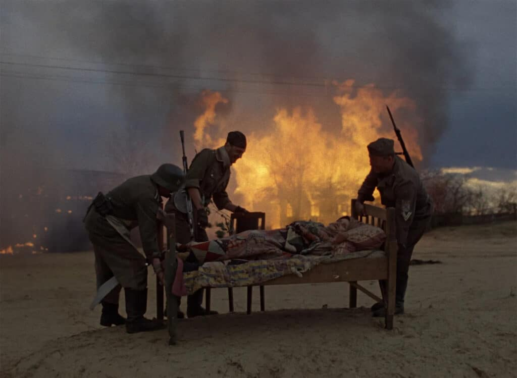 Drei Deutsche Soldaten stehen in Komm und sieh um ein Bett, in der eine alte Frau liegt, während im Hintergrund eine Scheune brennt.