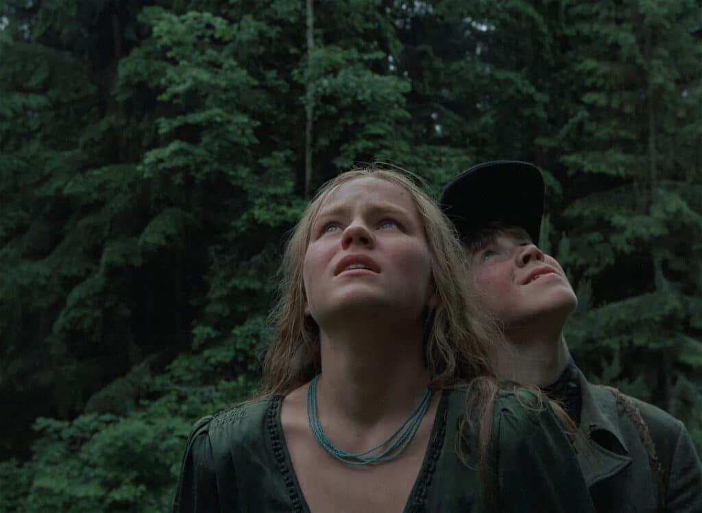Fljora und Glascha stehen in Komm und sieh im Wald und blicken in die Luft.