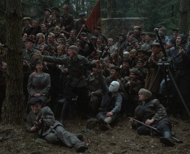 Dutzende Partisanen posieren für ein Foto. Einer trägt einen Verband um den Kopf und hält eine Handgranate hoch, während Fljora mit einem Gewehr auf dem Boden liegt.