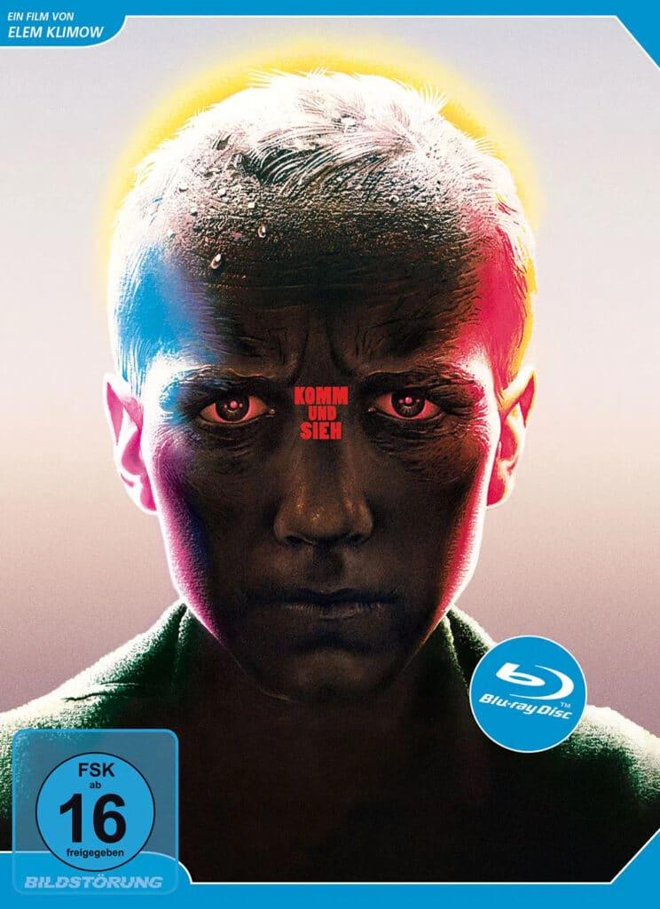 Das Blu-ray-Cover von Komm und sieh zeigt Fljoras Gesicht im Medium Close Up, während es in rot-blauem Licht beleuchtet wird und ein goldener Kranz um seinem Kopf wie ein Heiligenschein erscheint.
