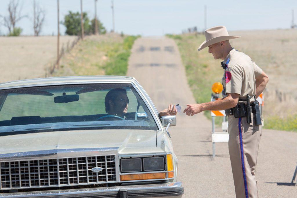 Toby (Chris Pine) sitzt im Auto, neben ihm ein Polizist, Toby reicht ihm seine Papiere in Hell or High Water
