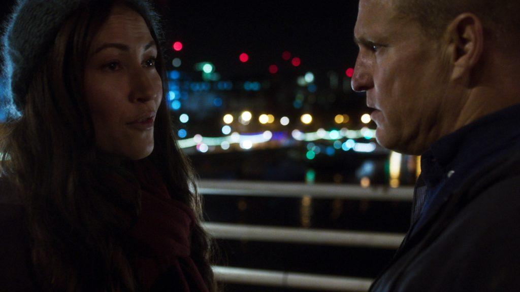 Woody Harrelson und Eleanor Matsuura stehen sich auf einem Dach gegenüber, London bei Nacht im Hintergrund, Lost in London