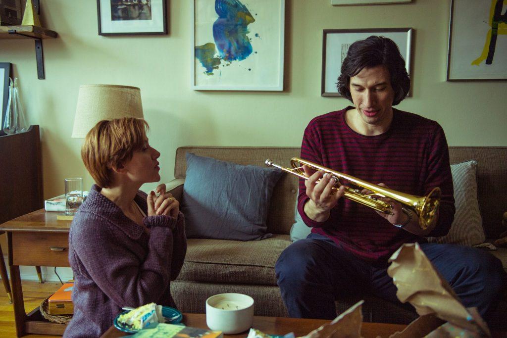 Adam Driver und Scarlett Johansson auf dem Sofa, Driver hält eine Trompete, Johansson sieht ihn an