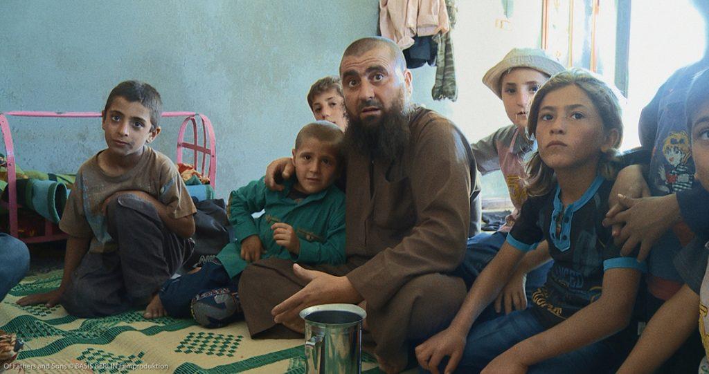 Salafistenführer Abu Osama im Kreis seiner Söhne. Der Älteste, Osama Osama, ist halb verdeckt, trägt einen Hut und legt seinem Vater vertrauensvoll von hinten eine Hand auf die Schulter.