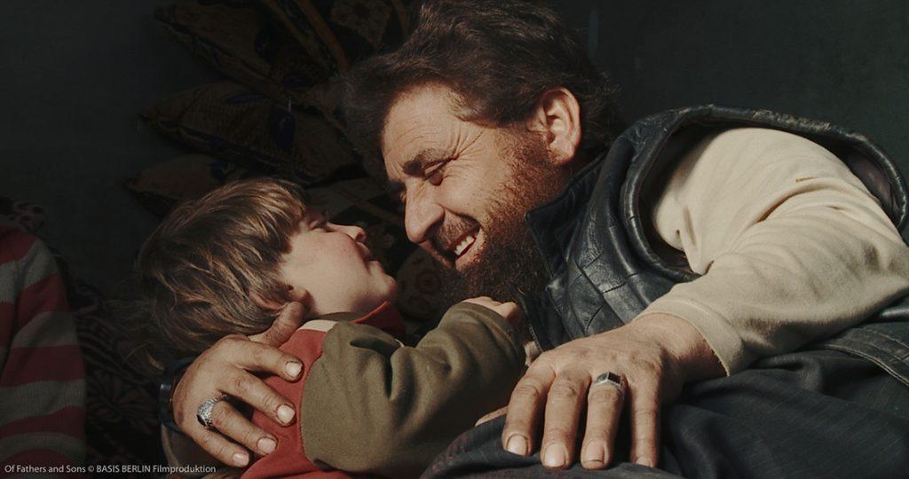 Salafistenführer Abu Osama, rechts im Bild) kuschelt liebevoll mit einem seiner jüngeren Söhne, den er im Arm hält.