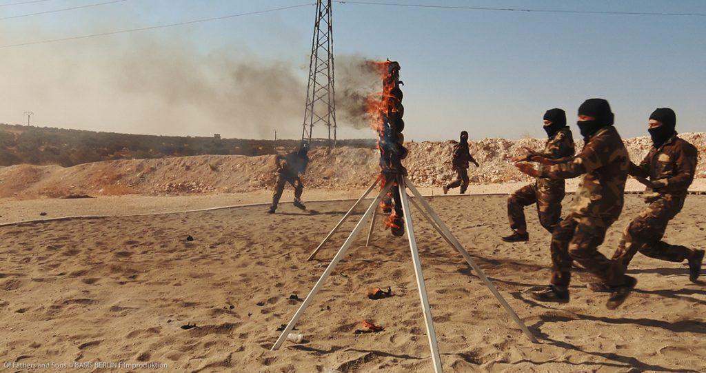 Im Trainingslager der Salafisten. Rechts nimmt eine Gruppe vermummter Jungen in Tarnazügen Anlauf, um durch brennende Reifen zu springen. Links von den Reifen wartet ein Ausbilder.