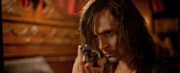Adam zielt mit einem Revolver in Richtung Kamera