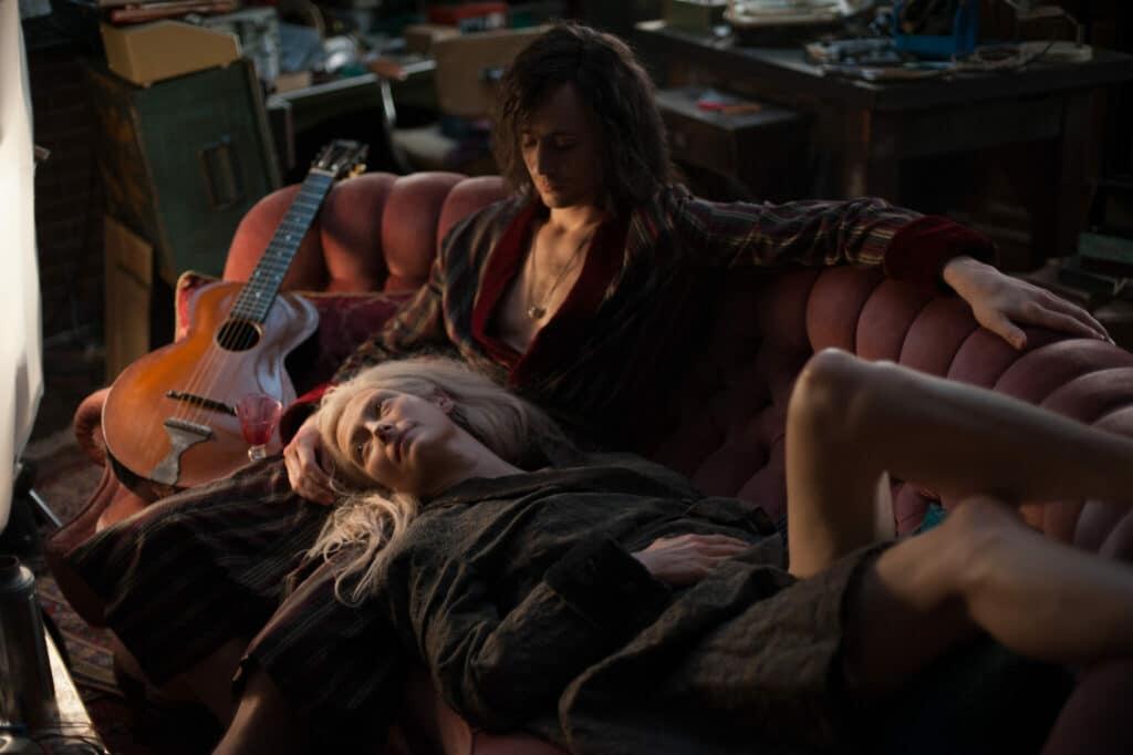 Adam und Eve liegen gemeinsam auf dem Sofa, er sieht sie verliebt an