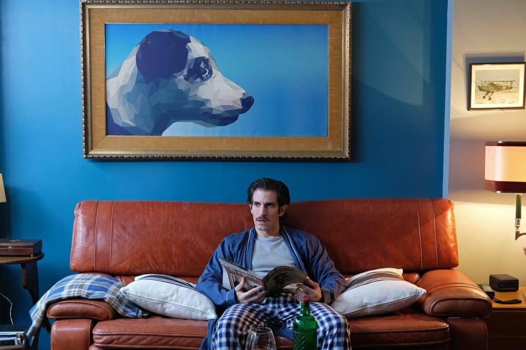 Emilio sitzt auf seinem Sofa, über ihm hängt ein riesiges Bild von einem Hund in Die obskuren Geschichten eines Zugreisenden.