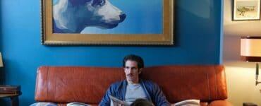 Emilio sitzt auf seinem Sofa, über ihm hängt ein riesiges Bild von einem Hund